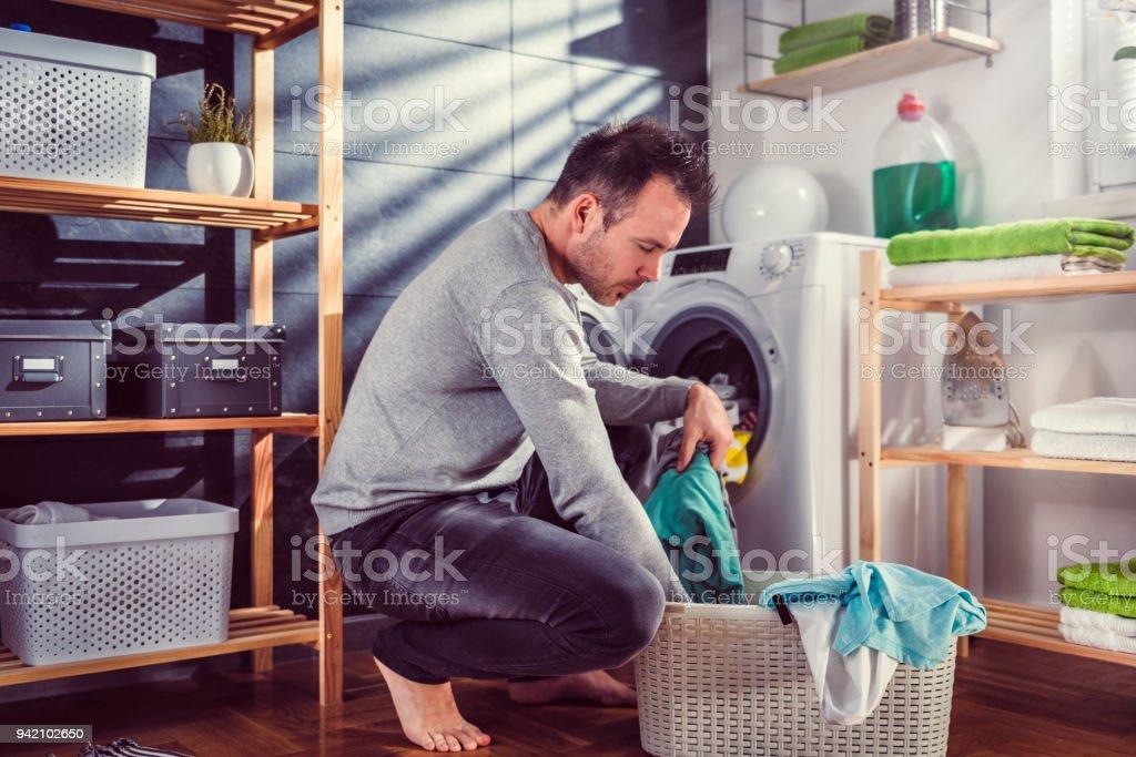 Man putting clothes into washing machine stock photo