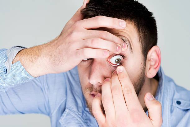 Hombre poniendo en sus ojos de lentes de contacto - foto de stock