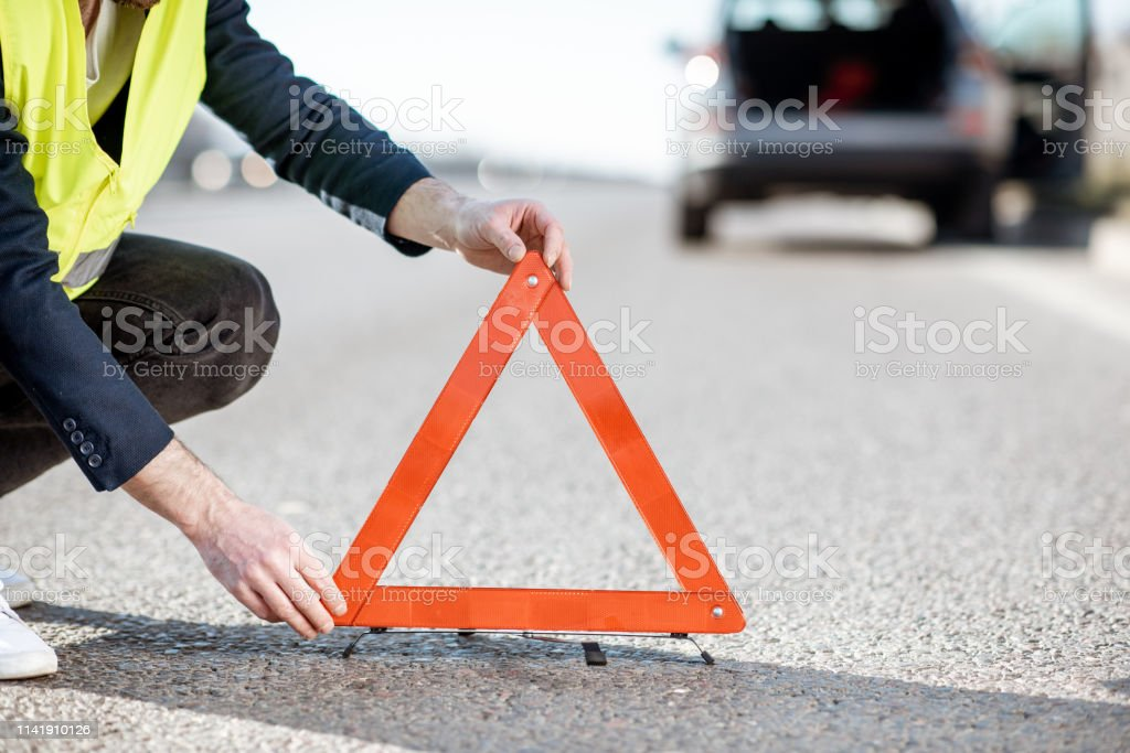 Man in road vest putting emergency triangle sign on the highway with...