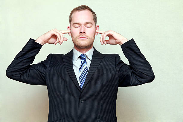 Man Putting Fingers in Ears stock photo
