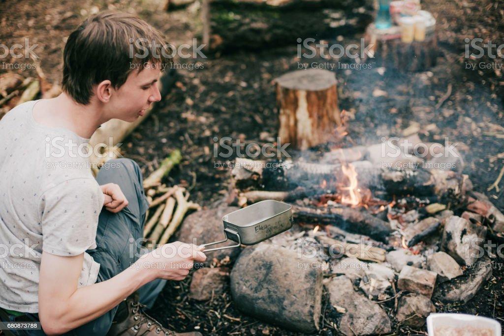 Man putting frying pan into smoky campfire.