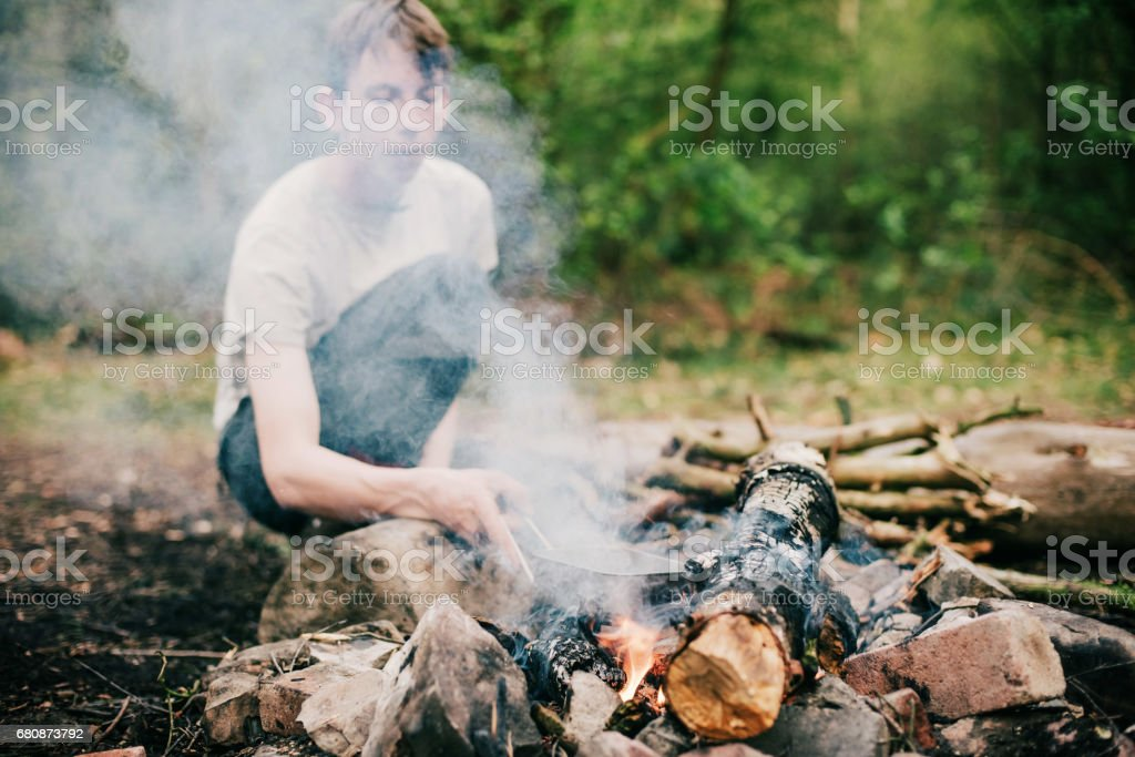 Man putting frying pan into smoky campfire. royalty-free stock photo