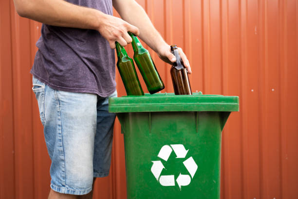 Man putting glass bottles in recycle bin Man putting glass bottles in recycle bin no face, closeup bottle bank stock pictures, royalty-free photos & images