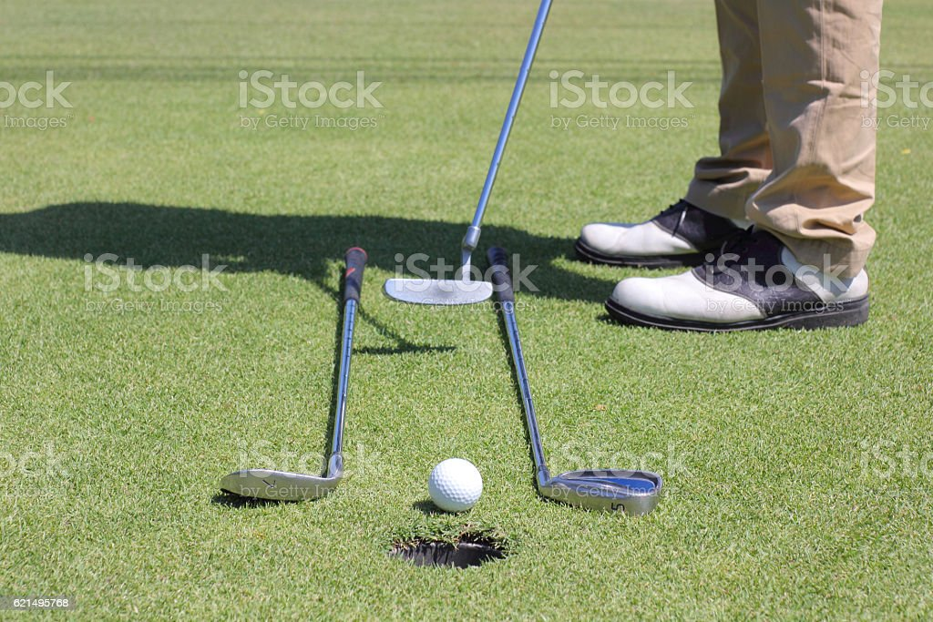 Man putting golf ball with hole. photo libre de droits