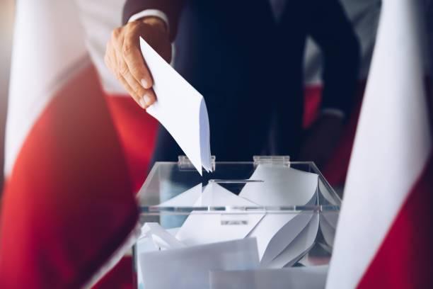 Mann, der seine Stimme an die Wahlurne stellt. – Foto