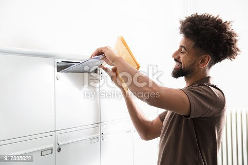 istock Man Putting Letters In Mailbox 917885622