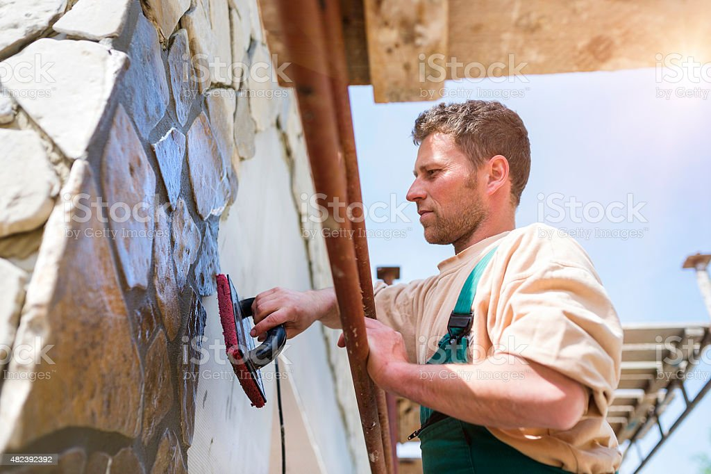 Man putting natural stones on a wall stock photo