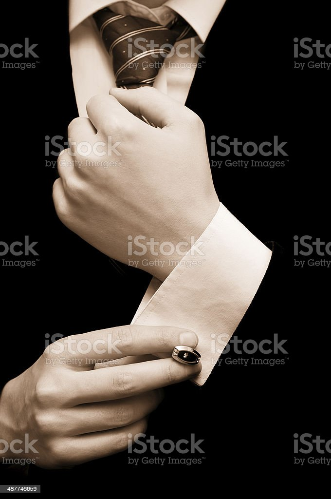 Man putting on cuff links stock photo