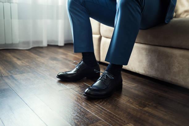 mann schuhe anziehen - knotenkleid stock-fotos und bilder