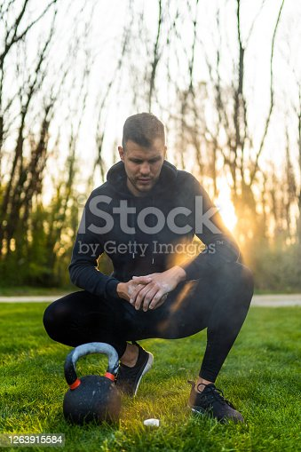 Front view of mid adult man putting on sports chalk before lifting kettlebell