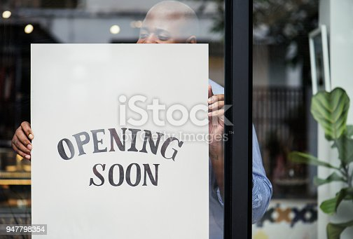 istock Man putting on store opening soon sign 947798354