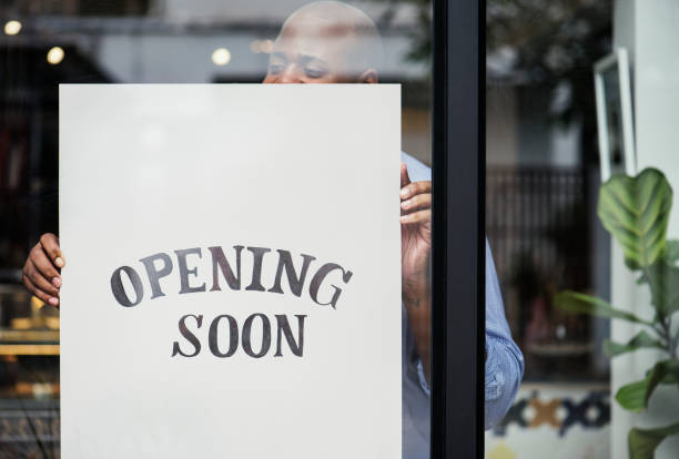 Man putting on store opening soon sign stock photo