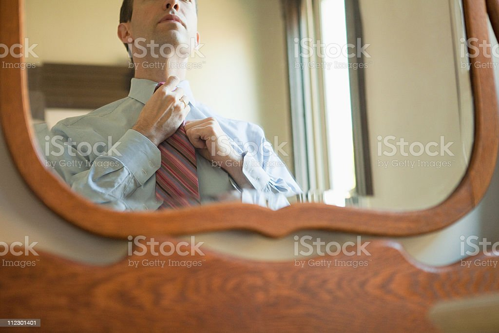 Man putting on tie in mirror stock photo