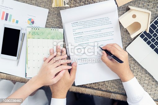 Man putting signature on document  loan contract and holding hands couple, real estate purchase, success business contract deals.