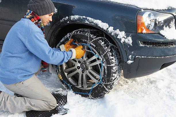 Mann Putting Schnee Ketten auf die Reifen des Autos. – Foto