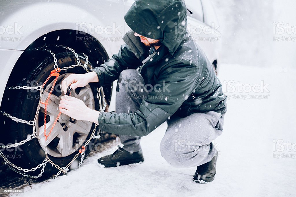 Man Putting Snow Tire Chains On Car stock photo