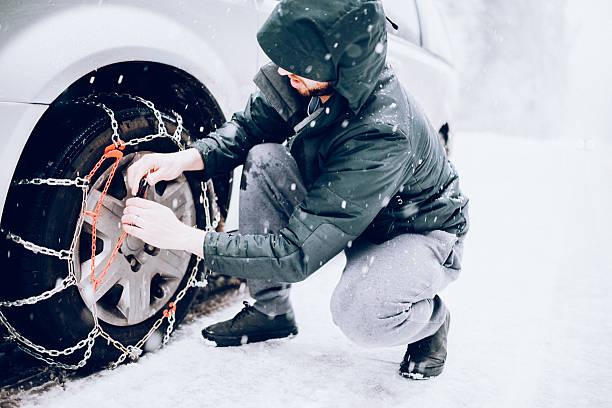 Man Putting Snow Tire Chains On Car - foto de stock