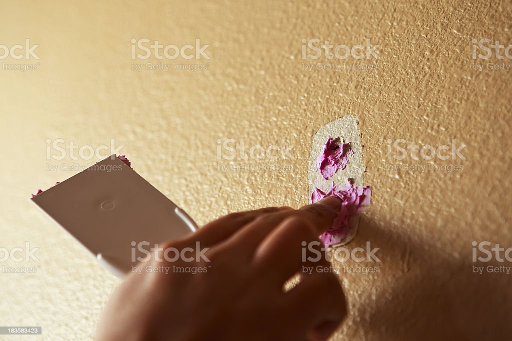 Man Putting Spackling Paste on a Hole stock photo