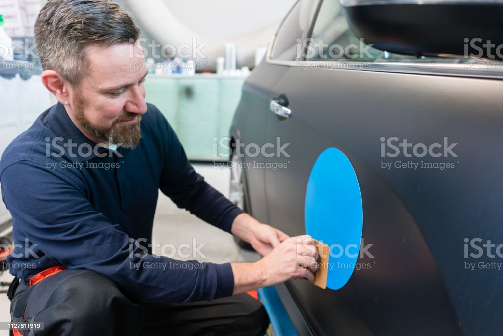 Man putting sticker with company slogan on a car stock photo