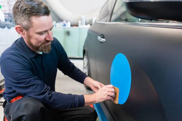 Mann ein Auto Aufkleber mit Firmenslogan aufsetzen – Foto