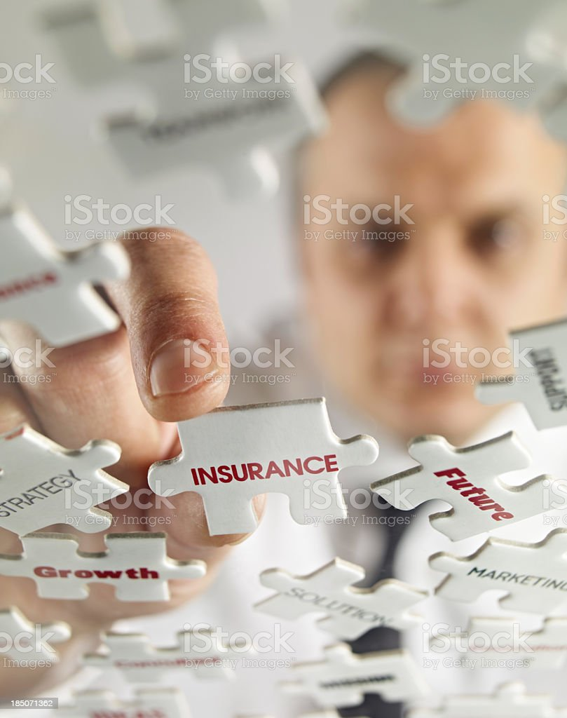 A man putting together a puzzle of insurance pieces stock photo