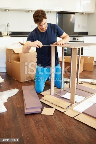 459373065 istock photo Man putting together furniture for new home 459521921