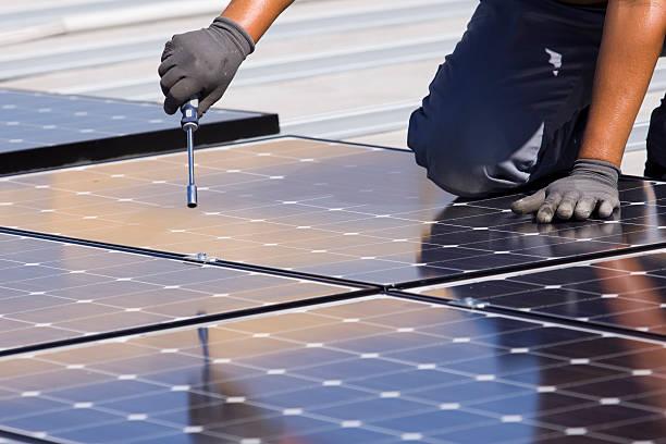 Man putting together solar panels stock photo