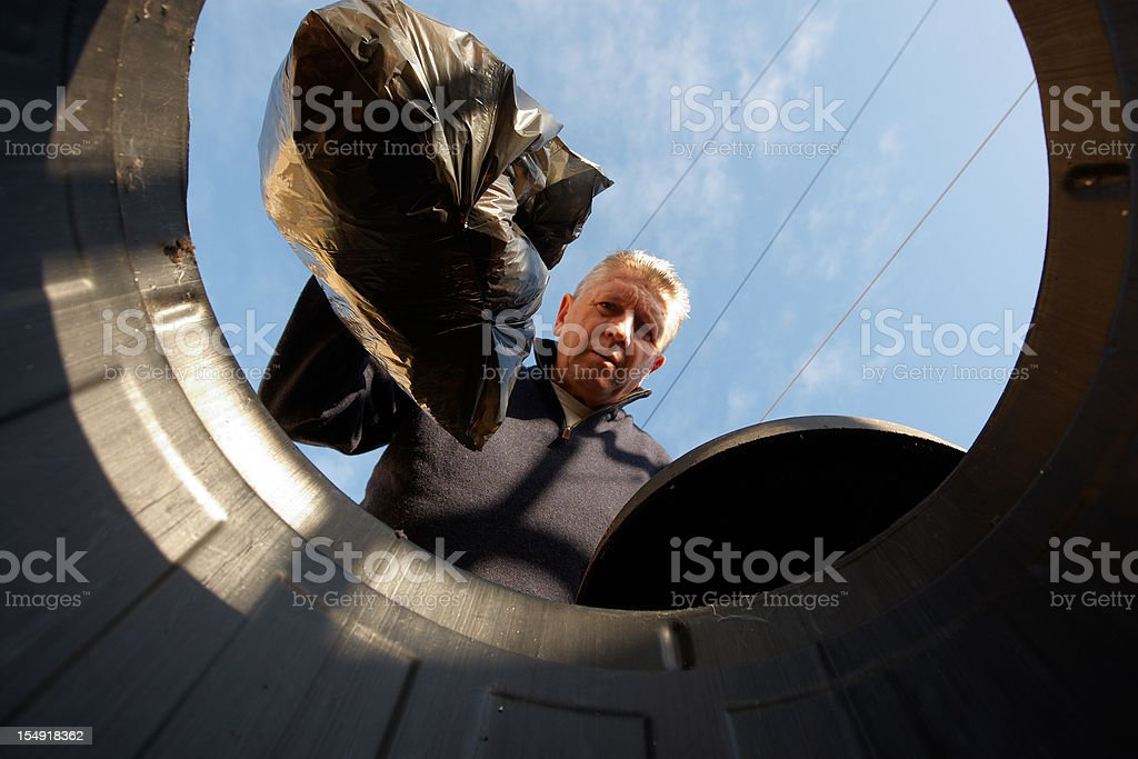 Man putting trash in bin stock photo
