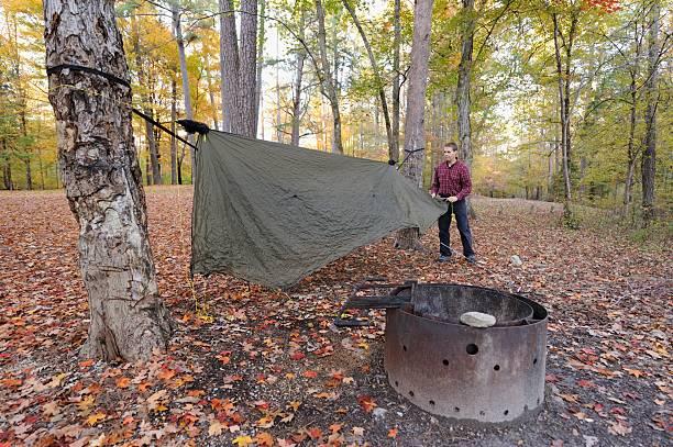 mann aufhängen plane zelt auf hängematte in campingplatz - planenzelt stock-fotos und bilder