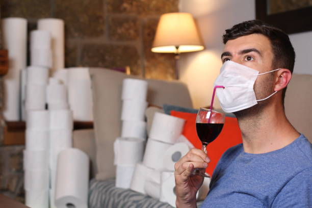 Homem em quarentena em casa com papel higiênico e álcool - foto de acervo