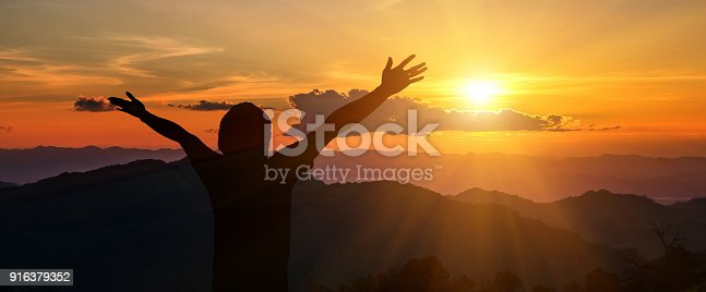 Man raised his arms to the mountains, freedom, success, thank God.
