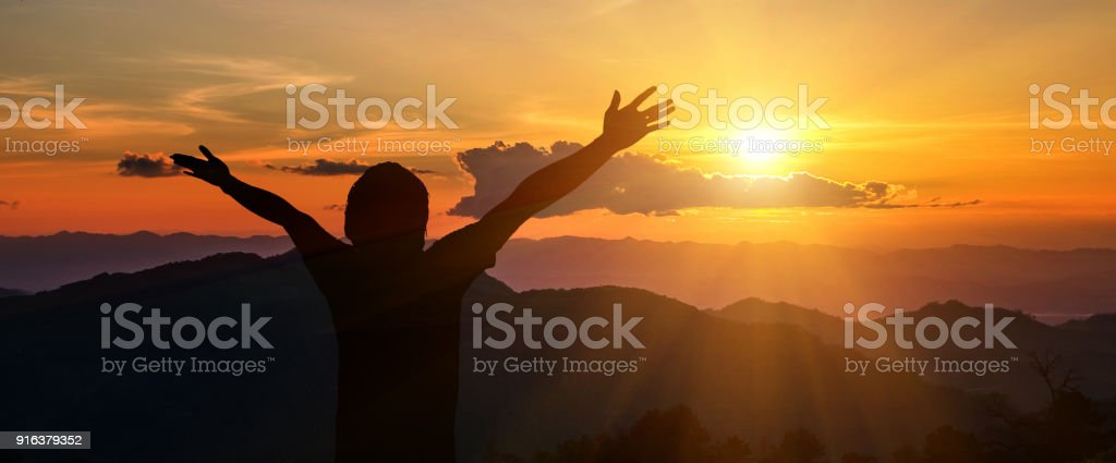 Man raised his arms to the mountains stock photo
