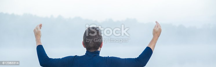 873786782 istock photo Man raised his hands feels the freedom. Foggy air. 612383314