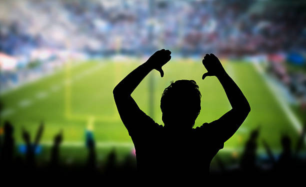 Man Raising Arms in Excitement at Sporting Event stock photo