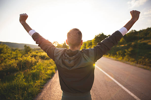 Man raising arms Sport and life achievements and success concept. Sporty man raising arms towards beautiful sunset on the road one man only stock pictures, royalty-free photos & images