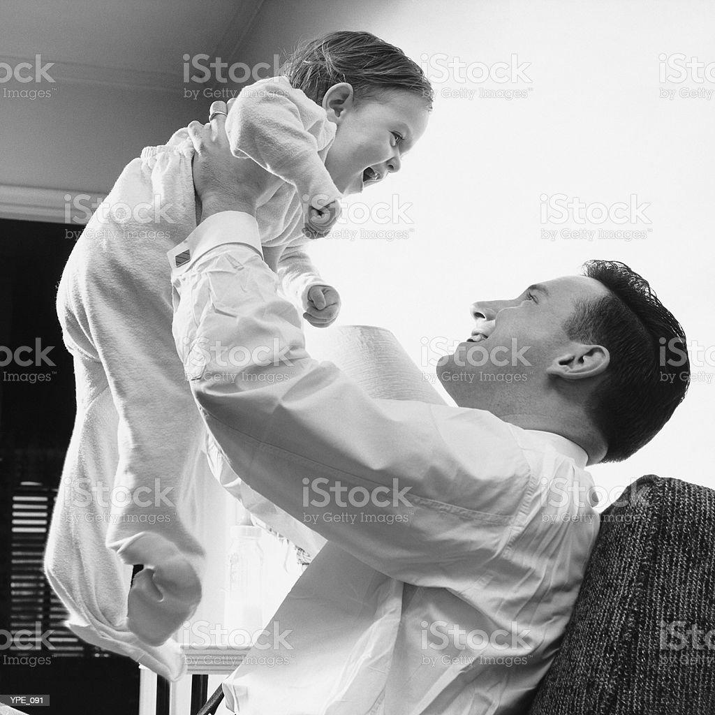 Hombre plantear bebé sobre la cabeza foto de stock libre de derechos