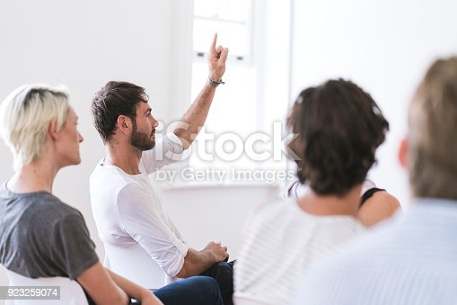 istock Man raising hand during group therapy session 923259074