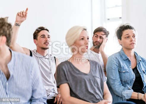 istock Man raising hand during group therapy session 923259204