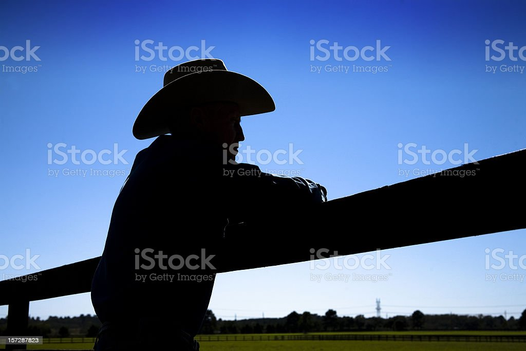Man rancher on farm. Fence in silhouette. Cowboy hat.  Ranch. stock photo