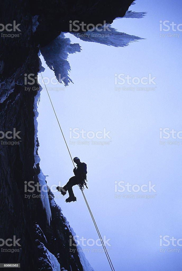 Man rappelling off ice climb. photo libre de droits