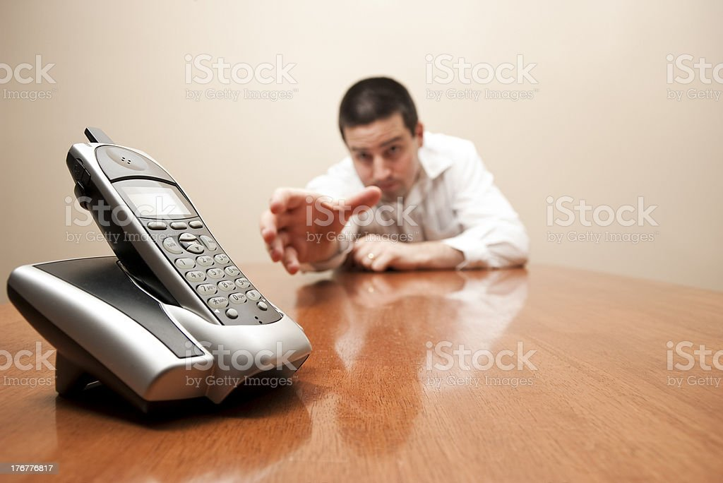 Man reaches for cordless phone royalty-free stock photo