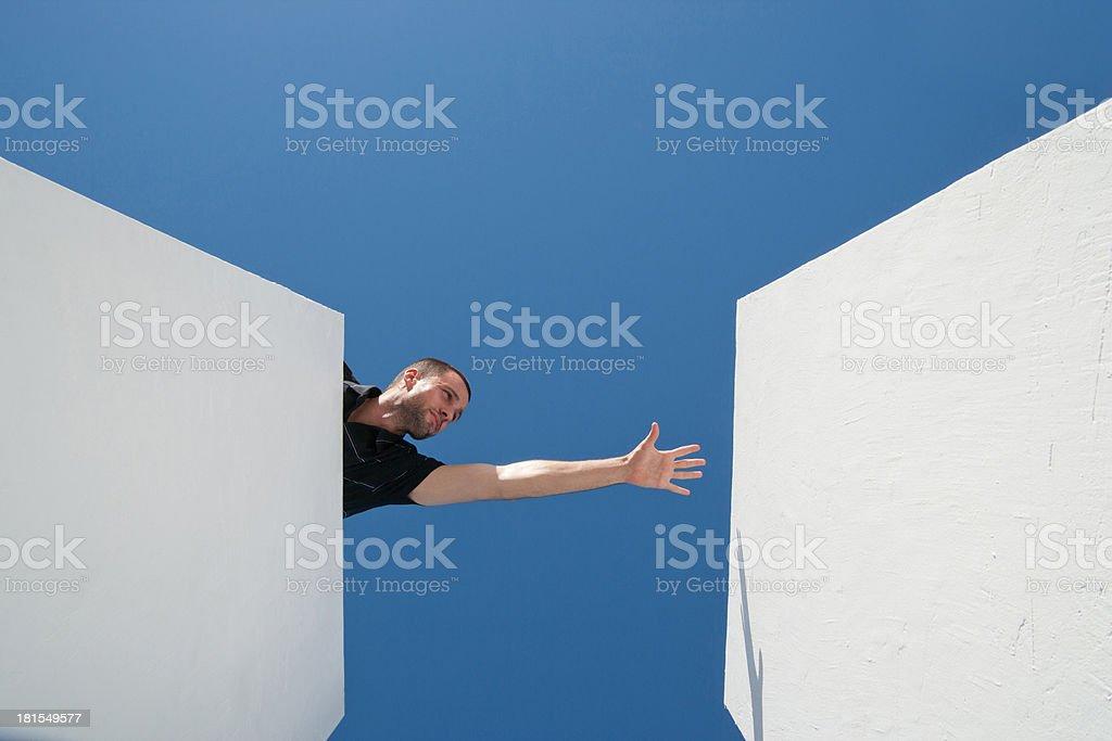 Man reaching across blocks outdoors stock photo