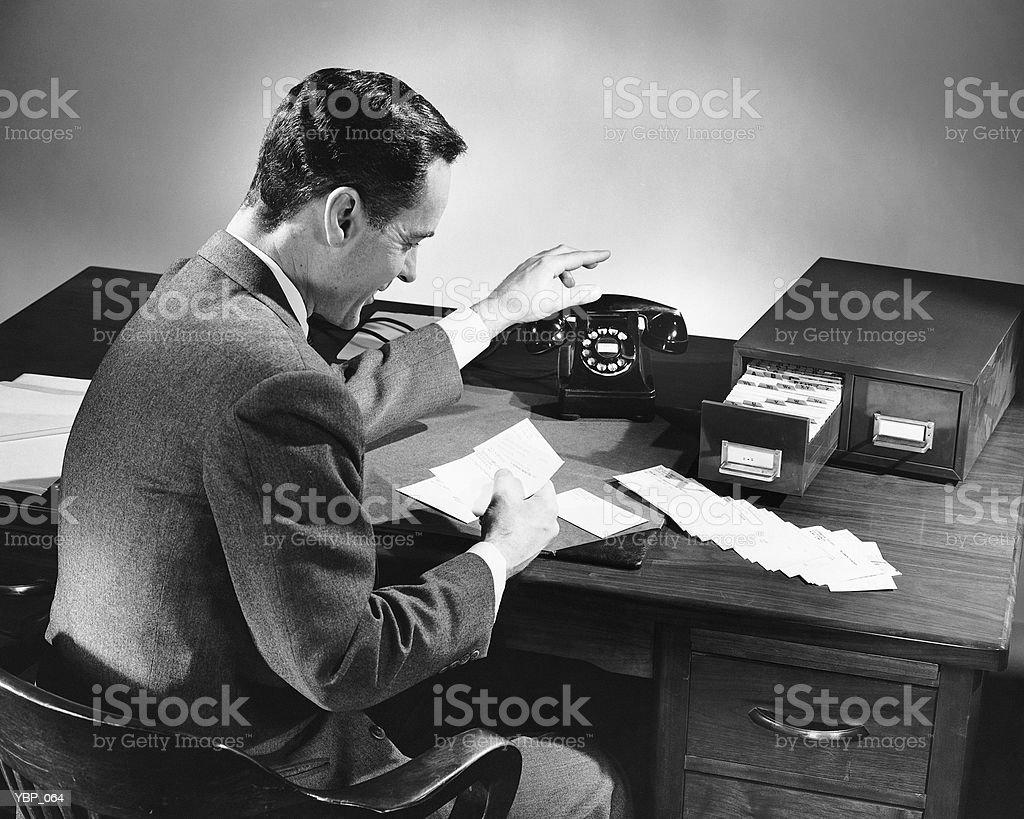 Homem alcançar para telefone ao ler o cartão foto de stock royalty-free