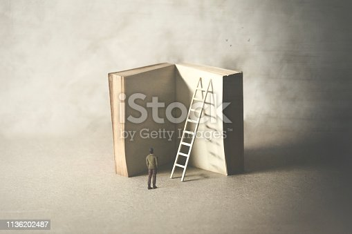 istock man reaching higher knowledge level, climbing a book, surreal concept 1136202487