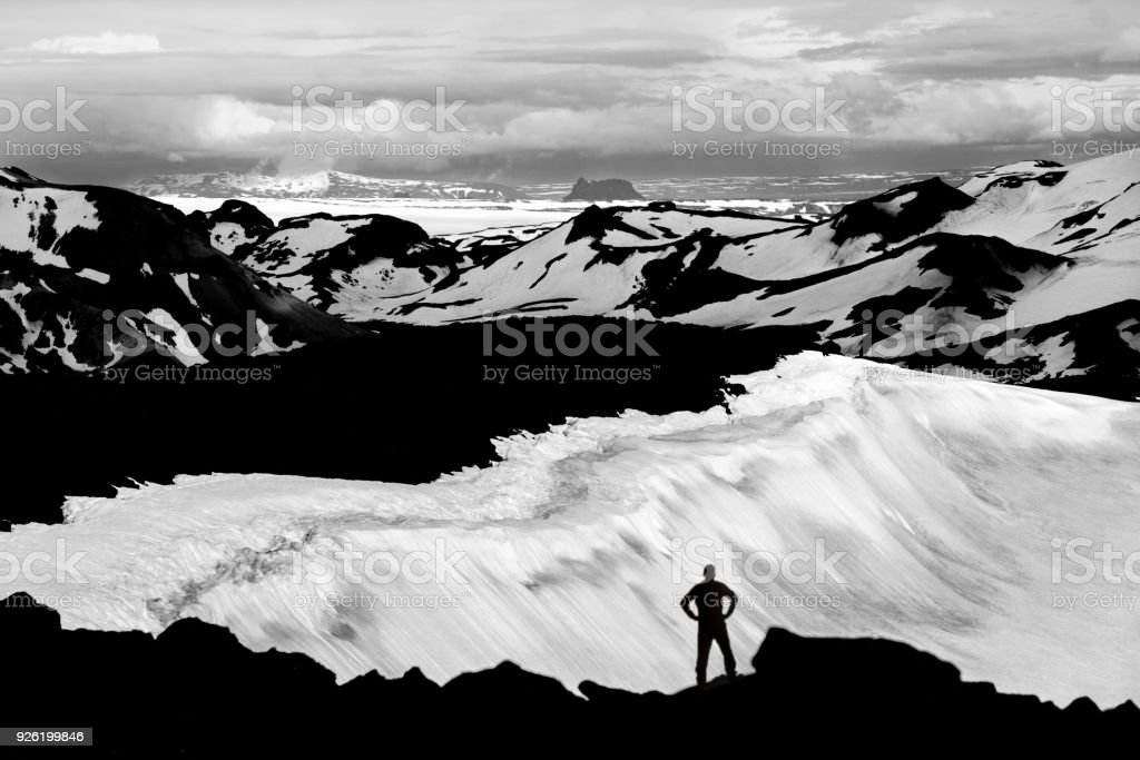 Man reaching mountain summit, watching glaciers and snowfields in Iceland. stock photo