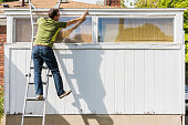 Man reaching to paint white trim on ladder