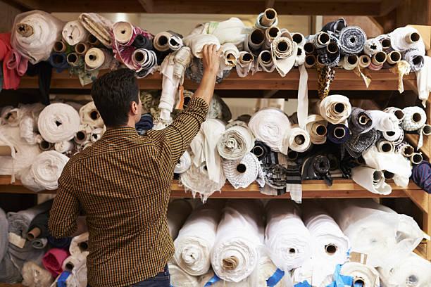 man reaching to select fabric from storage shelves - stoffregal stock-fotos und bilder