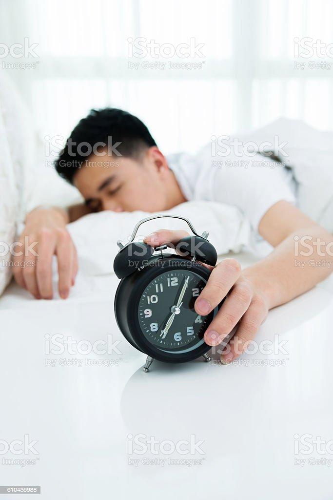 Man reaching to turning off alarm clock stock photo