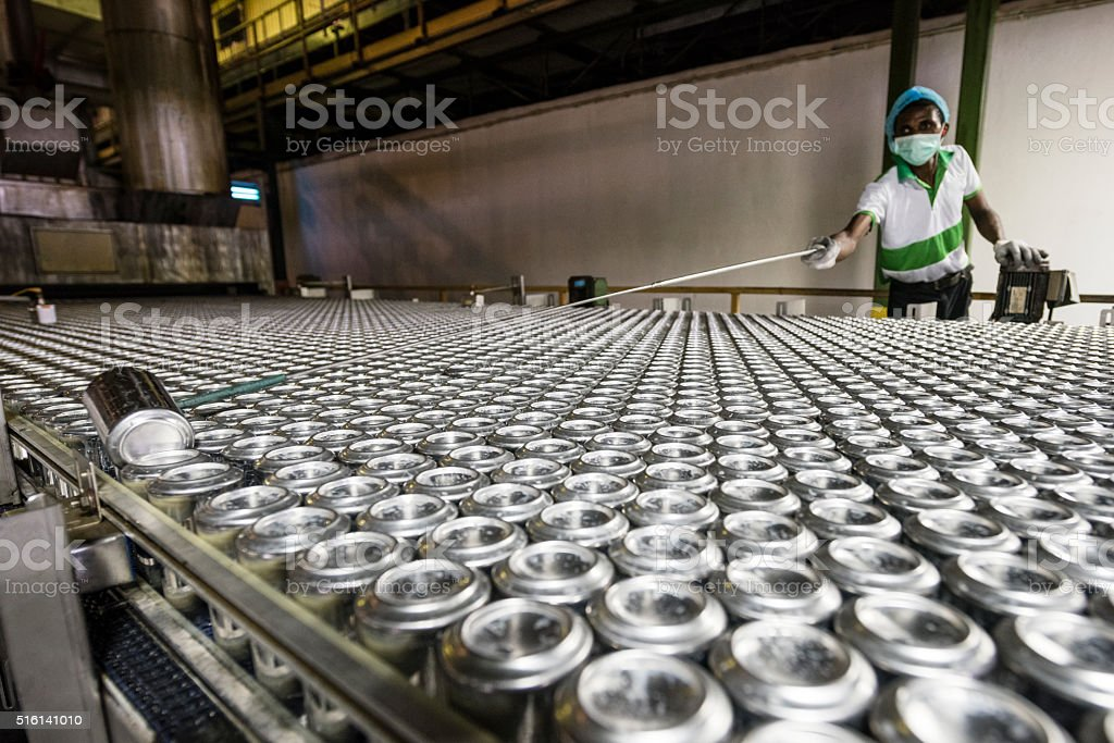 Man reaching with tool in aluminium can processing plant stock photo