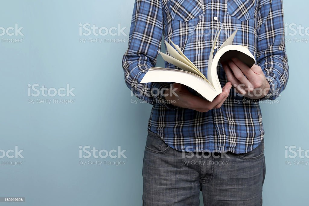 Man reading a book against blue background stock photo